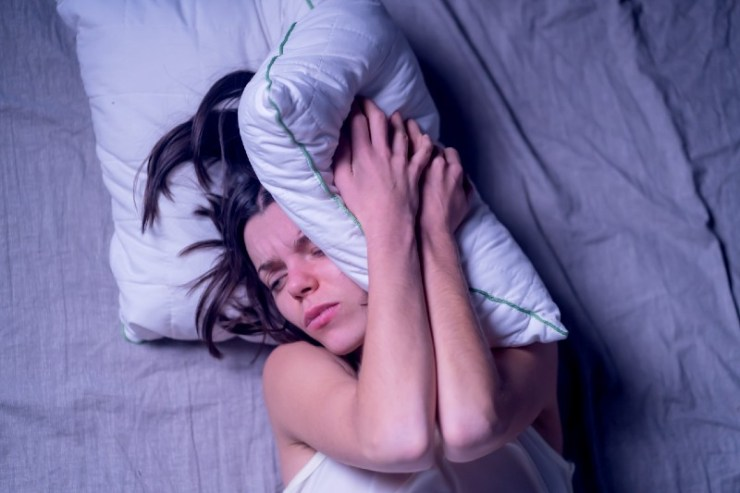 A young girl woke up in the morning in bed with a severe headache after the stress at work and nerves-shock