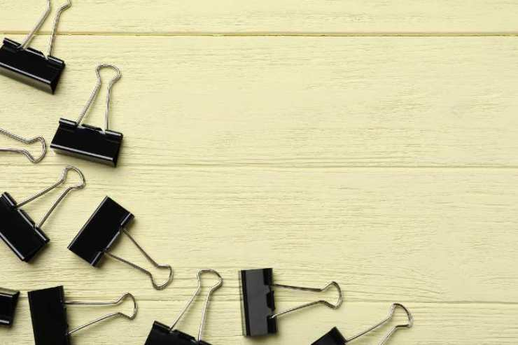 Black binder clips on yellow wooden table, flat lay. Space for text-binder clips
