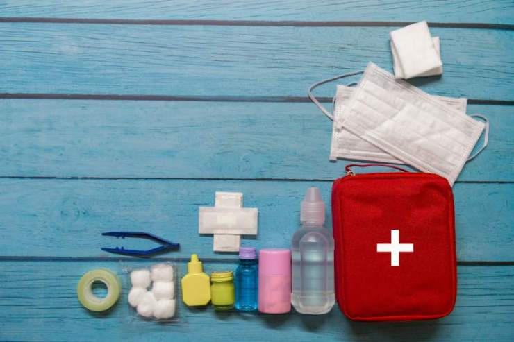 Top view first aid bag kid with medical supplies on wood background-first aid kit