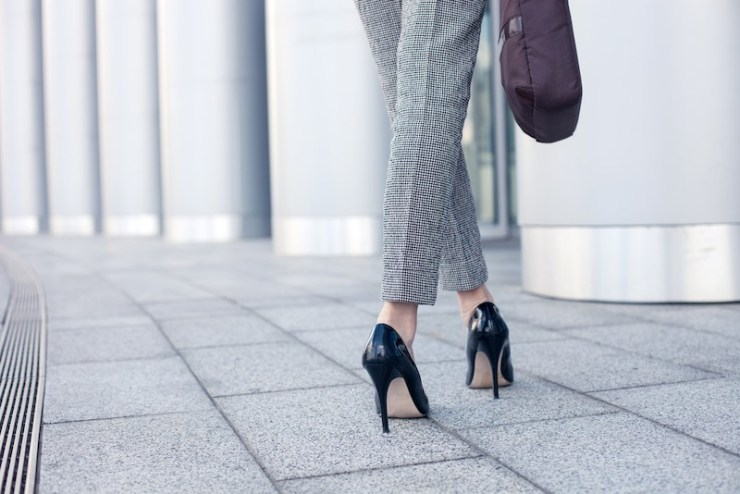 Close up of female legs of worker standing near her office. The woman is wearing formalwear and shoes on high heels. She is holding a handbag. Copy space in left side   lady's technique