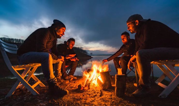 A-group-of-four-friends-are-sitting-around-the-campfire-and-having-fun-campfire