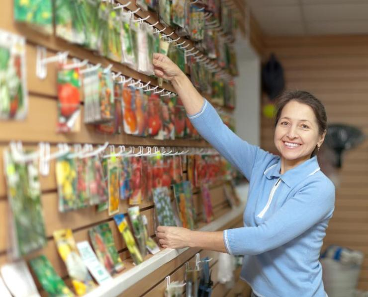 Smiling mature woman chooses packed seeds at store for gardener-seed starting