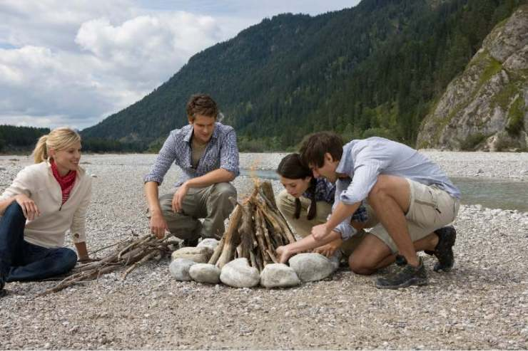 Young couples building campfire near stream-campfire