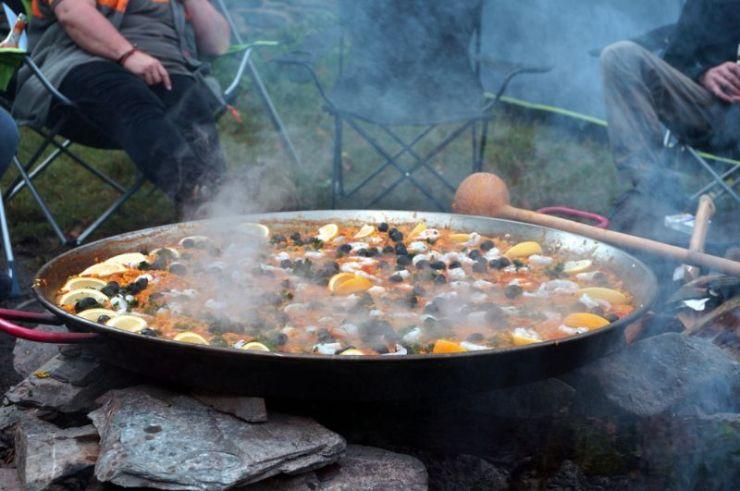 persons-sitting-outside-tent-making-paella | campfire paella