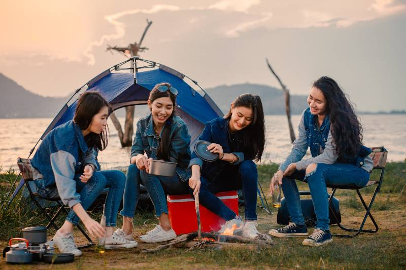 A group of young women camping, they sit around the fire-Camping With A Large Group