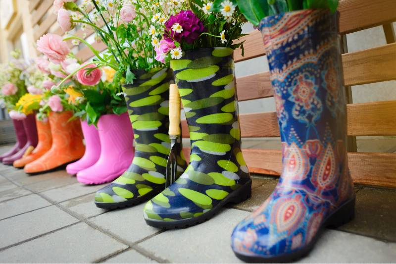 Gardening. Colourful rubber boots with bouquets of flowers in them stand in a row. Garden decor. Rain boots with flowers in a row-Small Space Garden