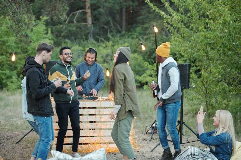 Large group of young joyful friends dancing and having fun on weekend-Camping With A Large Group