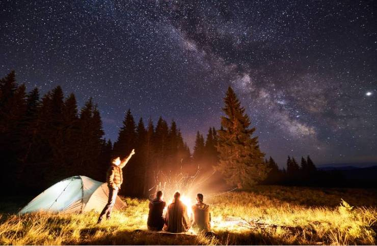 Male showing his friends Milky Way over camping. Guys are sitting by the campfire-terrain