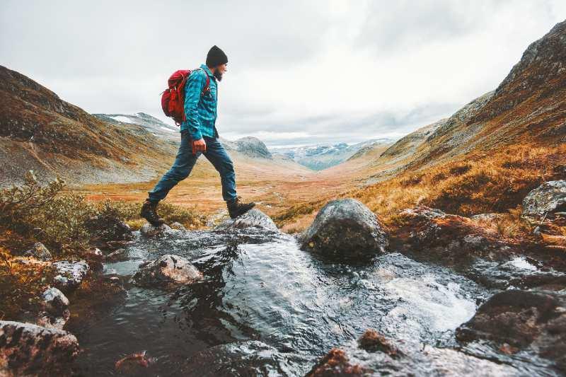 Man solo traveling backpacker hiking in scandinavian mountains-Camping Alone