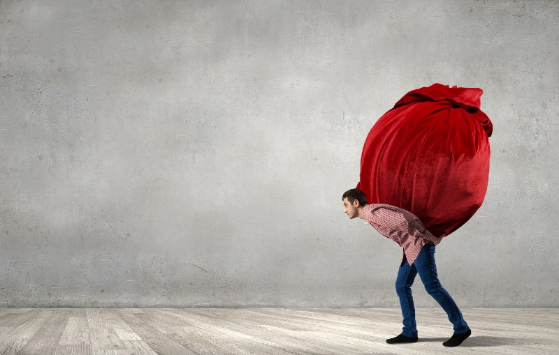 Young man in casual carrying heavy red bag-prepping for shtf