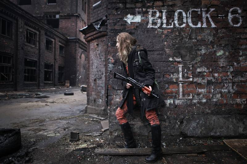 Young survivalist armed woman looking out of building corner with rifle in her hands-prepping for shtf