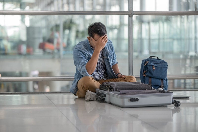 Young traveler man with casual clothes sitting on the floor at the terminal airport, unpack luggage ,problem passport lost during his vacation-prepping for shtf