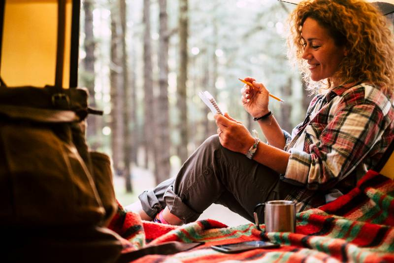 beautiful happy free woman in solo camping with tent in the forest write notes on notebook-Camping Alone