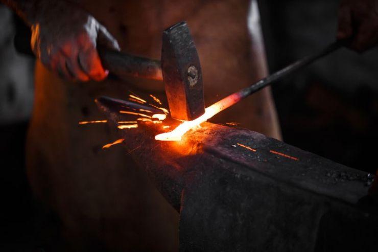 blacksmith-manually-forging-molten-metal-on   skills for surviving