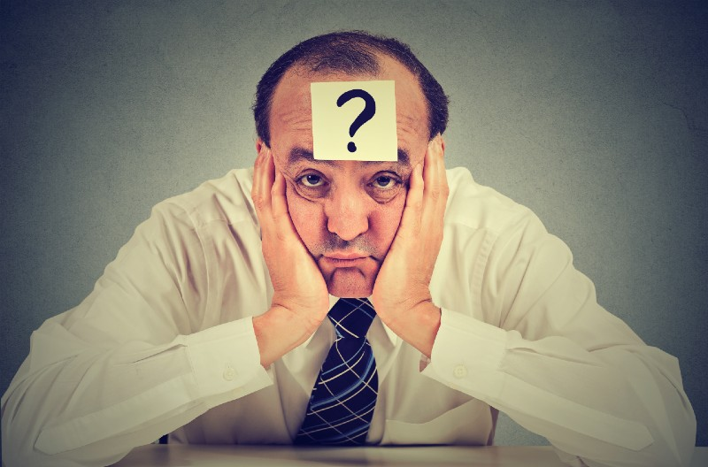clueless business man with question mark sitting at table-prepping for shtf