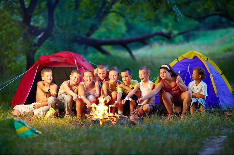 group of happy kids roasting marshmallows on campfire-Camping With A Large Group