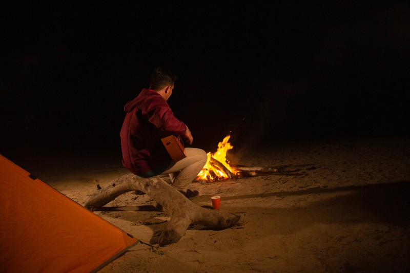 man camping alone on the beach accompanied by a bonfire and a guitar-Camping Alone
