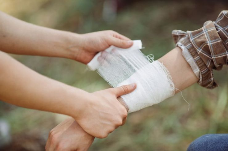 person-wrapping-his-friends-injured-arm   first aid
