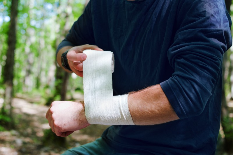 Applying an arm medical bandage in a forest during the journey-Survival Skill set