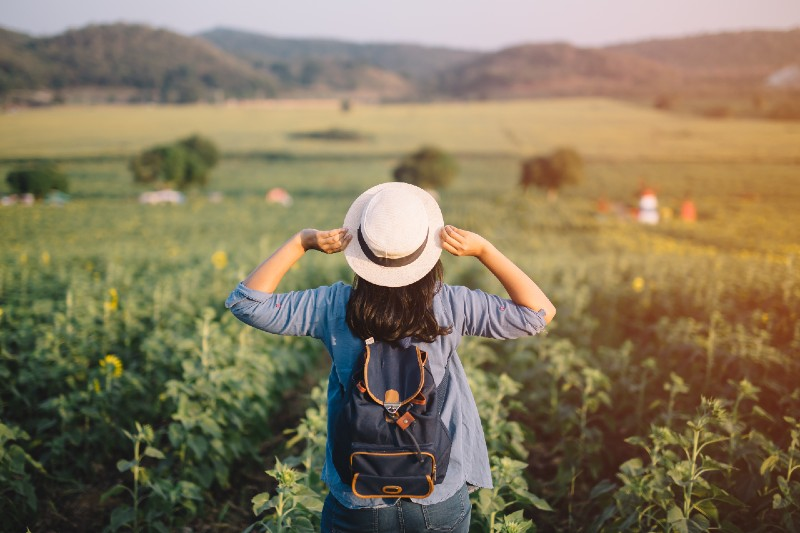 Asian woman traveler with backpack holding hat and looking at amazing mountains-Bug Out Bag