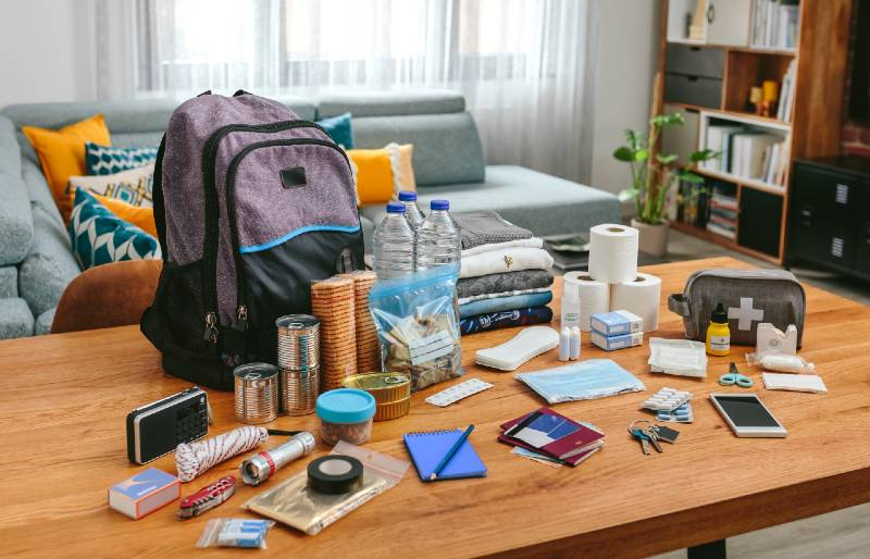 Emergency-backpack-equipment-organized-on-the-table-in-the-living-room-Bug-Out-Bag