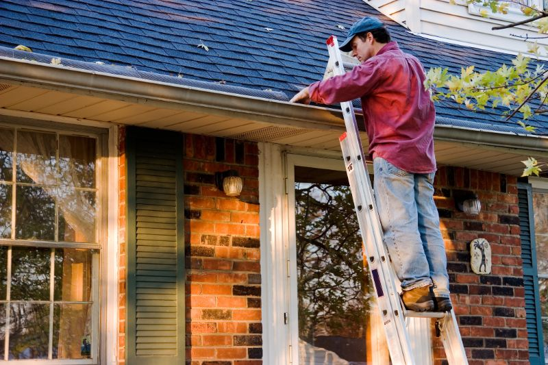 Man cleaning gutters   Hurricane preparedness