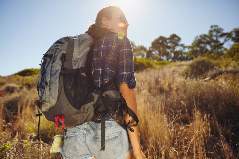 Rear view shot of young woman hiking on summer day-bug out bag contents