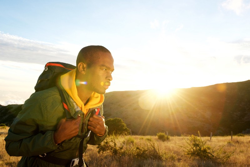 Side portrait of african american man hiking in mountains with sunset in background-Bug Out Bag