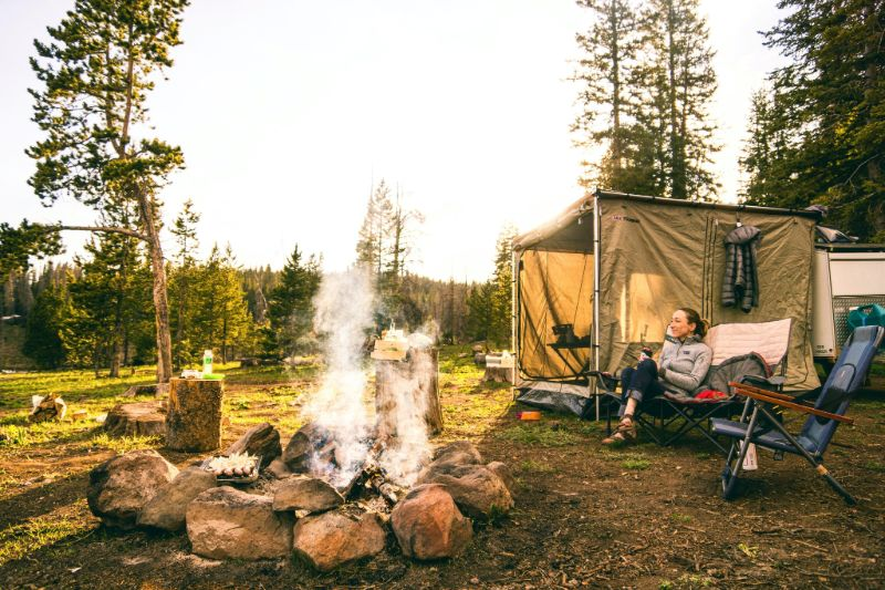 Girl sitting near campfire | Camping Cots