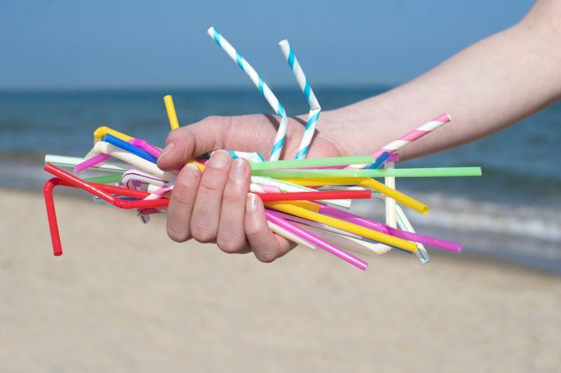 Hand holding plastic straws   REI camping