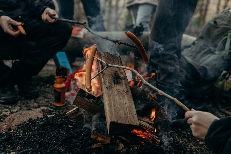 People Holding Stick with Sausages | Camping Food Hacks