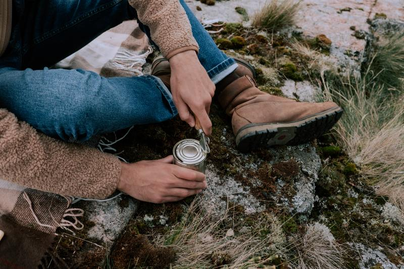 Person in Blue Denim Jeans and Brown Boots Holding Can | Camping Food Hacks