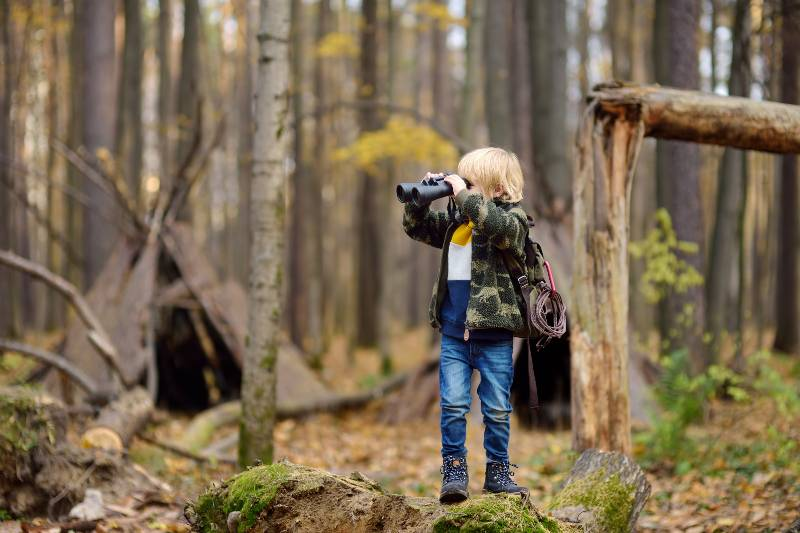 Little boy scout with binoculars during hiking in autumn forest-Kids for Surviving